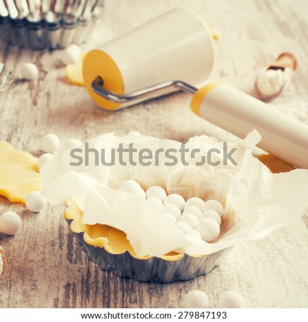 Baking background. Ingredients for dough bottom for tartlet, quiche, tart.  Shortbread dough, baking forms, ceramic baking beans, rolling pin.  Top view. Selective focus. Retro style toned.  - stock photo