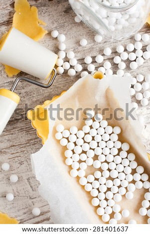 Baking background. Ingredients for dough bottom for tartlet, quiche, tart.  Shortbread dough, baking forms, ceramic baking beans, rolling pin.  Top view. - stock photo