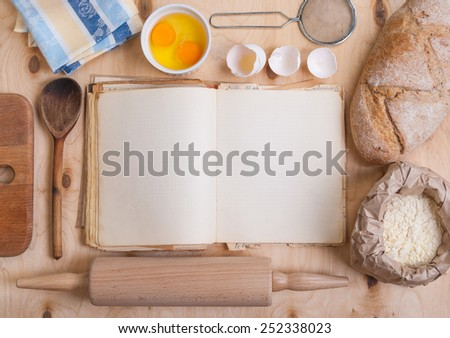 Baking background with blank cook book, eggshell, flour, rolling pin. Free space for text - stock photo
