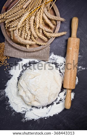 Baking background with flour, rolling pin and grain ears on black chalkboard - stock photo