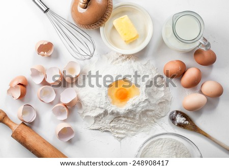 baking background with raw eggs,eggshell, sugar, flour , milk and butter - stock photo