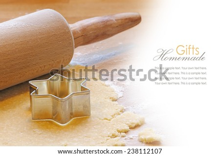 baking background with rolling pin and cookie cutter in star shape, sample text on the white, homemade gifts, for christmas or new year - stock photo