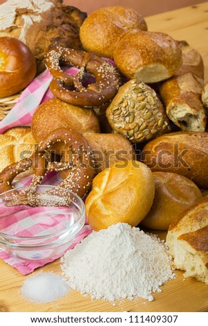 Baking bread with flour, water and salt - rolls, pretzels, white bread, arranged in a group, food still life in warm colors with ingredients - stock photo