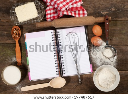 Baking cake in rural kitchen - dough recipe ingredients (eggs, flour, butter, sugar) and rolling pin on vintage wood table. Rustic background with free text space. - stock photo