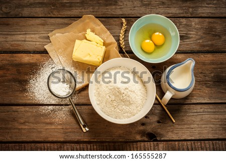 Baking cake in rural kitchen - dough recipe ingredients (eggs, flour, milk, butter, sugar) on vintage wood table from above - stock photo