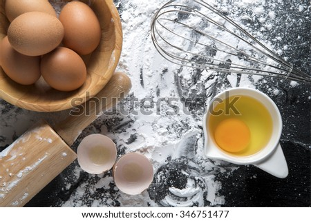 Baking cake ingredients. Bowl, flour, eggs, egg whites foam, egg beater, rolling pin and eggshells on black chalkboard  - stock photo