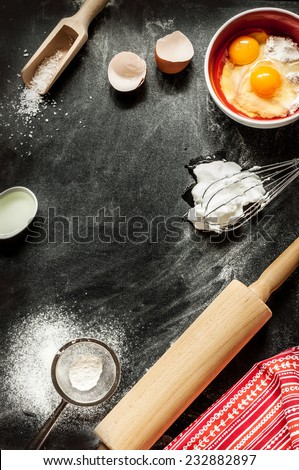 Baking cake ingredients. Bowl, flour, eggs, egg whites foam, eggbeater, rolling pin and eggshells on black chalkboard from above. Cooking course poster background - layout with free text space. - stock photo