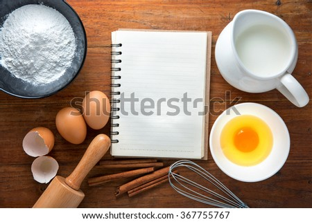 Baking cake ingredients,recipe book,Bowl, flour, eggs, egg whites foam, egg beater, rolling pin and eggshells on wooden table - stock photo
