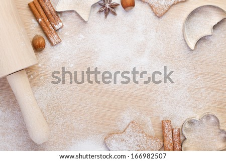 Baking christmas cookies- rolling pin, cookie cutters,cinnamon, anise, hazelnuts on wooden background - stock photo