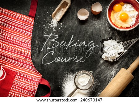 Baking course poster design with cake ingredients on black chalkboard from above. Apron, bowl, flour, eggs, egg whites foam, eggbeater, rolling pin and eggshells. - stock photo