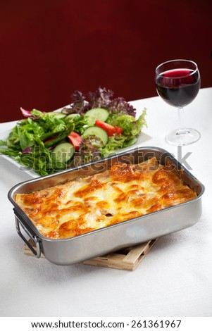 baking dish with lasagna and salad  - stock photo