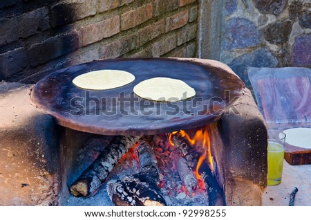 Baking flour tortillas. Oven with firewood. - stock photo