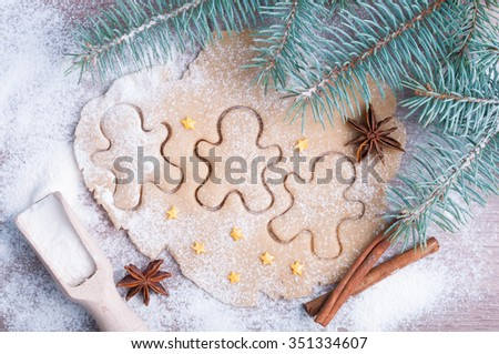 Baking gingerbread christmas cookies. Flour, dough, gingerbread men, stars, cinnamon, anise and branch of spruce on a wooden background. Christmas background. Top view - stock photo