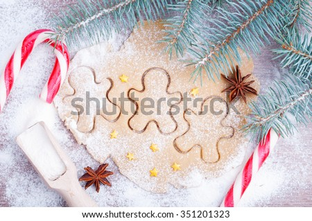 Baking gingerbread cookies. Flour, dough, gingerbread men, Christmas canes, anise and branch of spruce on a wooden background. Christmas card. Top view - stock photo