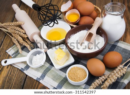 Baking ingredients - eggs, flour,milk,sugar and butter on a wooden background - stock photo