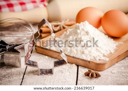 Baking ingredients - flour, eggs, butter and rolling pin, cookie cutters on a table - stock photo