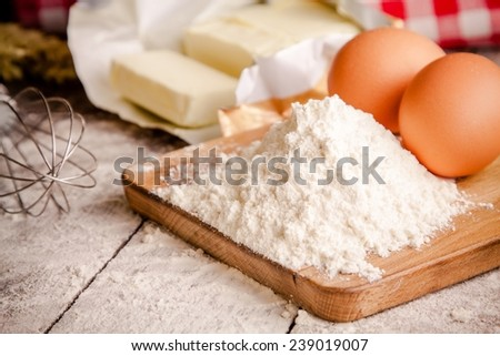Baking ingredients - flour, eggs, butter on a table - stock photo