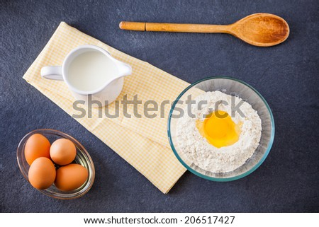 Baking ingredients - flour, milk and eggs with a wooden spoon and napkin on a slate background - stock photo