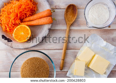 Baking ingredients for a carrot cake - flour, butter, brown sugar, grated carrots, half an orange, a wooden spoon on a rustic wooden background - stock photo