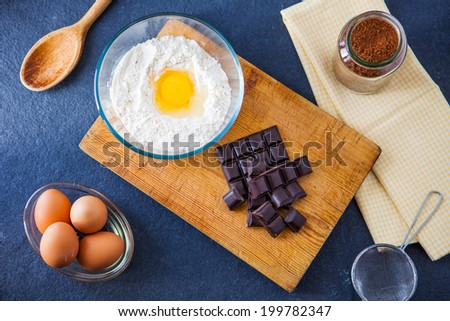 Baking ingredients for a chocolate cake - flour, eggs, chocolate, cocoa powder with a wooden spoon, sieve and napkin on a slate background - stock photo
