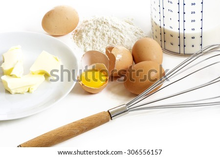 Baking ingredients for easter baking or pancakes, butter, eggs, flour, milk and a whisk on a white kitchen plate - stock photo