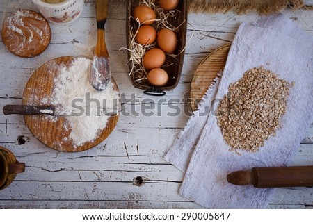 Baking ingredients in the kitchen with a bowl of eggs, free gluten flour, oat flakes, sugar, jug of milk and butter ready to bake a cake or make batter - stock photo