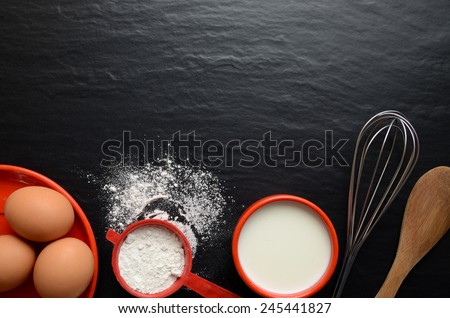 Baking ingredients on a dark, stone table: eggs, flour and milk. A lot of copyspace. - stock photo