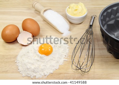 Baking ingredients with eggbeater and cake tin on a wooden kitchen-board - stock photo
