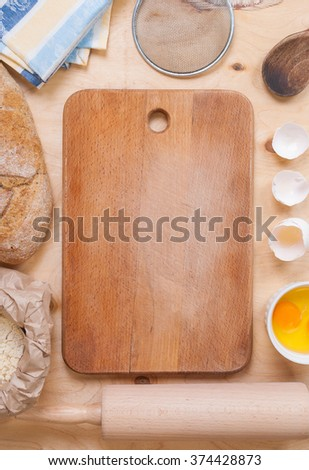 Baking light warm background with cutting board, eggshell, bread, flour, rolling pin. Ingredients for the baking. Rustic background with free text space. - stock photo