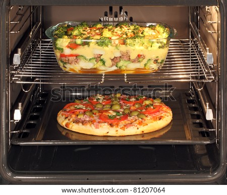 Baking pizza and casserole dish with bechamel sauce in oven. Hot air allows the burning of different dishes simultaneously. - stock photo