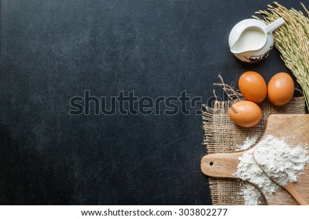 Baking powder milk and eggs on chalkboard for background - stock photo