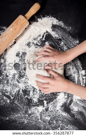 Baking preparing background. Female hands knead dough on the worktop. - stock photo