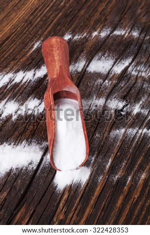 Baking soda on wooden spoon on brown wooden textured background. - stock photo