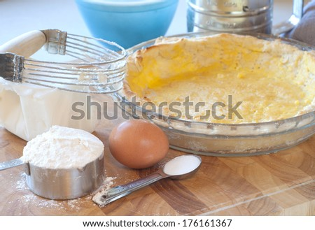 Baking still life with a fresh baked pie crust ready for quiche or custard filling surrounded by the ingredients  - stock photo