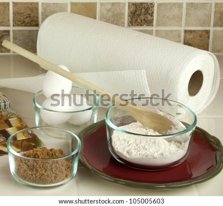 Baking tools and ingredients including flour brown sugar eggs in glass bowls set up on kitchen counter against tiled back splash. - stock photo