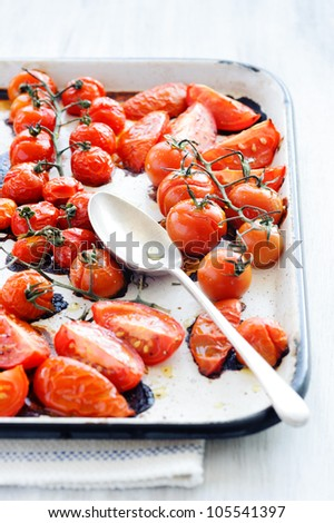 Baking tray filled with delicious juicy oven roasted tomatoes with large serving spoon, focus on spoon - stock photo