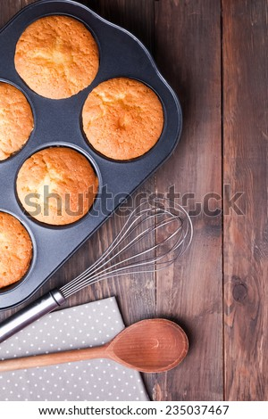 Baking tray with baked muffins, whisk and wooden spoon on the wooden table, top view  - stock photo