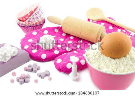 baking utensils like dough roller, wooden spoon, cup cake forms, cup cake cutters, flour, egg, oven mitt and fondant - stock photo