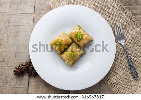 Baklava with pistachios and walnuts on white plate - stock photo