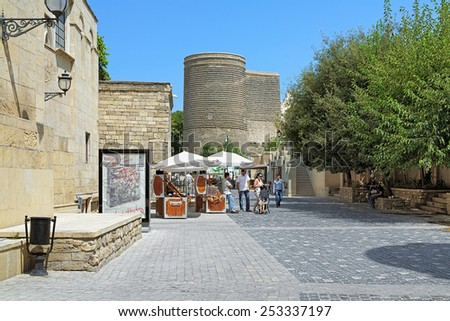 BAKU, AZERBAIJAN - AUGUST 23, 2014: Asef Zeynalli Street in the Baku Old City and view of Maidens Tower. The Maiden Tower built in 12th century is the Azerbaijan's most distinctive national emblems. - stock photo