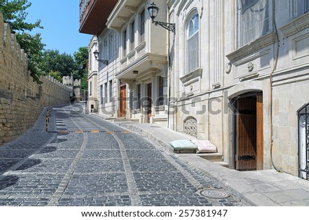 "BAKU, AZERBAIJAN - AUGUST 23, 2014: Kicik Qala Street and fortress wall of the Baku Old City. On this place was filmed episode ""Dammit!"" of the famous Soviet comedy film ""The Diamond Arm"" in 1968. - stock photo"