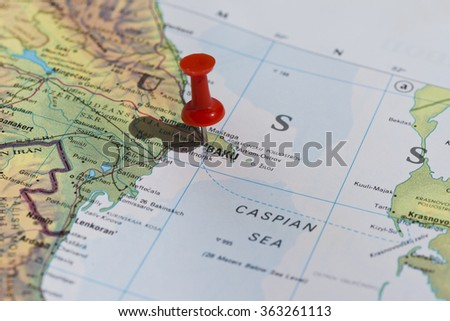 Baku marked on map with red pushpin. Selective focus on the word Baku and the pushpin. Middle East can be read at top of map. Pin is in an angle and casts some shadow to the left.  - stock photo