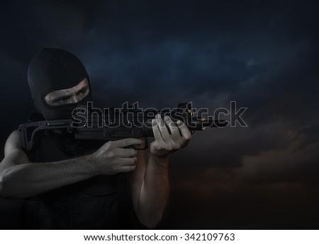 Balaclava and terrorist with machine gun on Cloud Background - stock photo
