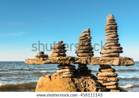 Balance a few stack of pebbles on rocky coast - stock photo