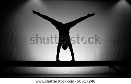 balance beam silhouette cartwheel - stock photo