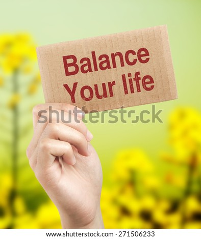 Balance your life brown card is holden by woman hand with beautiful natural background. - stock photo