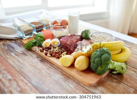 balanced diet, cooking, culinary and food concept - close up of vegetables, fruit and meat on wooden table - stock photo
