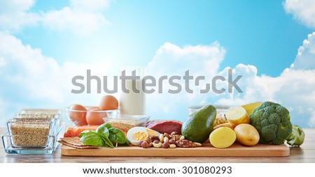 balanced diet, cooking, culinary and food concept - close up of vegetables, fruits and meat on wooden table over blue sky and clouds background - stock photo