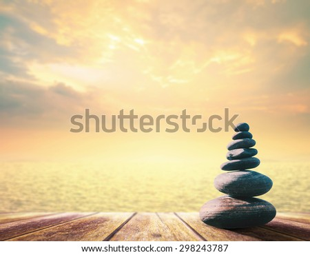 Balanced seven Zen stones on wooden paving and blurred beautiful autumn sunset background. World Mental Health Day, World Philosophy Day, Business, Education, Religion, Wisdom, Physiology concept - stock photo