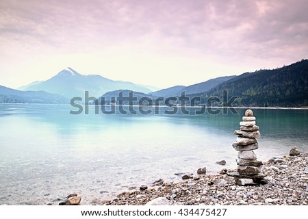 Balanced stone pyramide on shore of blue water of mountain lake. Blue mountains in water level mirror - stock photo